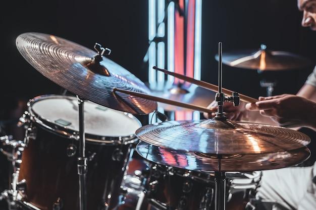 O baterista toca com bela iluminação em um fundo desfocado.