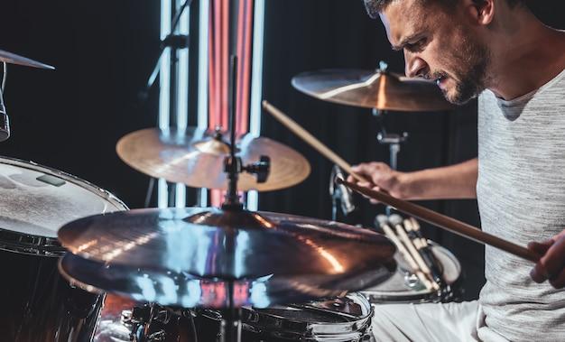 O baterista usando baquetas enquanto toca bateria durante a apresentação.