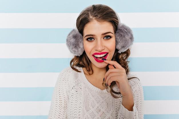 O batom fúcsia enfatiza o sorriso branco como a neve de uma jovem encantadora com fones de ouvido de inverno macios.