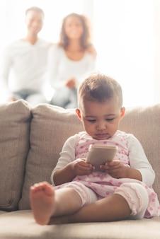O bebê afro-americano bonito está usando um telefone esperto.