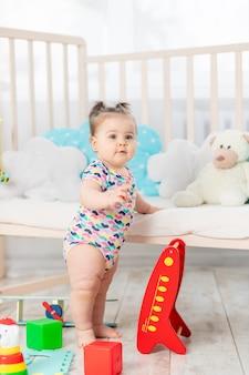 O bebê aprende a ficar de pé ou em pé, a criança brinca em casa no berçário