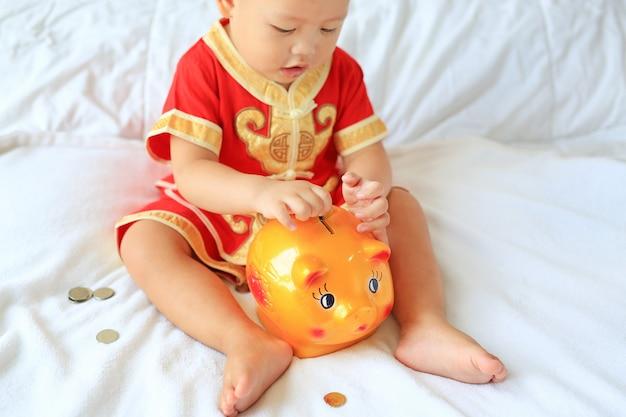 O bebê asiático pequeno no chinês tradicional veste a colocação de algumas moedas em um banco piggy na cama.