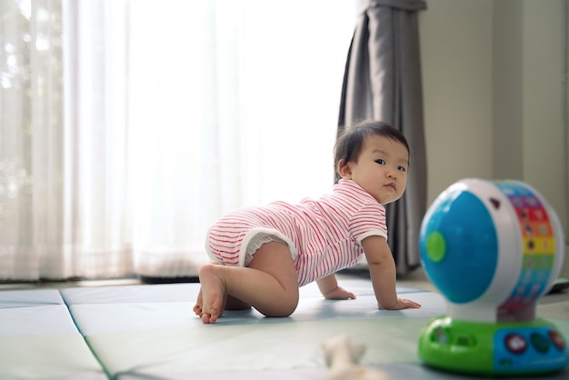 O bebê bonito asiático do scamp que rasteja na esteira macia em casa e que gira o olhar para trás para ver o que acontece.
