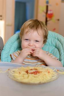 O bebê bonito de um ano come espaguete em uma cadeira infantil.