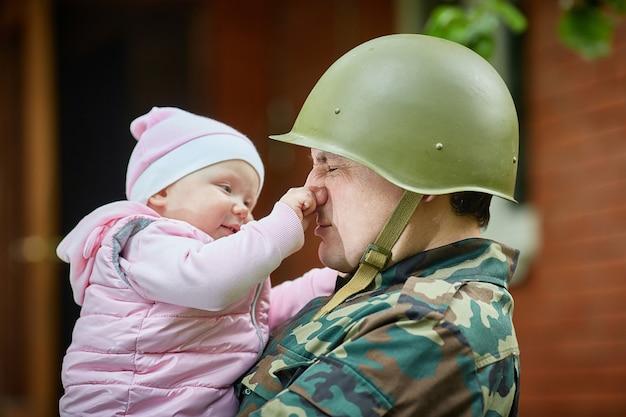 O bebê brinca com um soldado e puxa seu nariz.