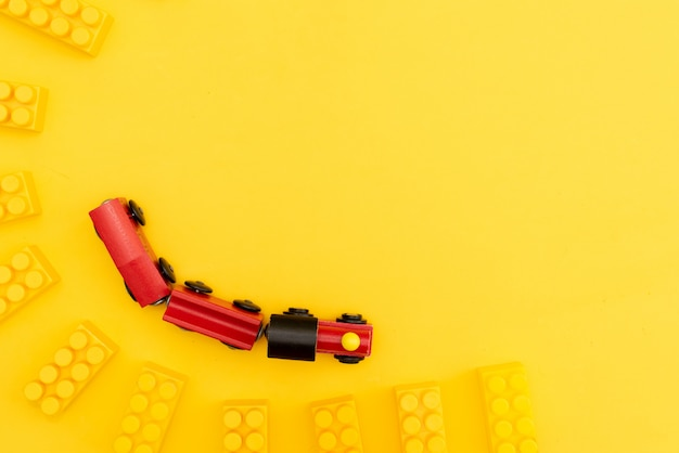 O bebê caçoa o quadro dos brinquedos com urso de peluche, carro de madeira do brinquedo, tijolos coloridos no fundo amarelo.