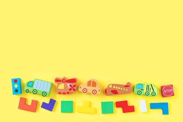 O bebê colorido caçoa brinquedos de madeira no fundo amarelo. desenvolvimento de blocos coloridos, carros e avião. vista do topo. postura plana. copie o espaço para texto
