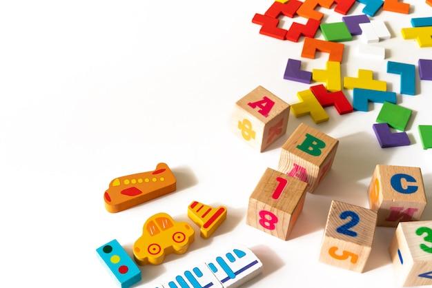 O bebê colorido caçoa brinquedos no fundo branco. quadro de desenvolvimento de blocos coloridos, carros e avião, quebra-cabeças. vista do topo. postura plana. copie o espaço para texto