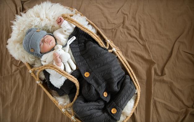 O bebê dorme docemente em um berço de vime, com um chapéu de tricô quente, sob um cobertor quente com um brinquedo em sua alça.