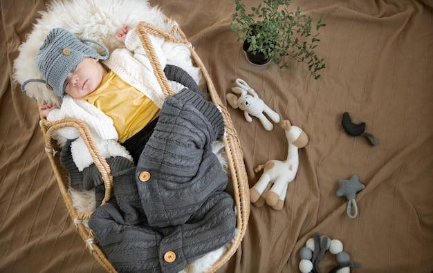O bebê dorme docemente em um berço de vime em um chapéu de malha quente com um cobertor quente.