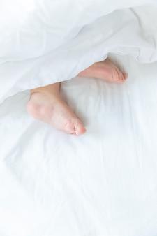 O bebê dorme em uma cama branca com os pés