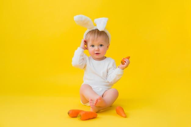 O bebê em uma roupa branca com orelhas de coelho na cabeça come cenouras, senta-se sobre um fundo amarelo com legumes. bebê na forma de um coelhinho da páscoa, espaço para texto