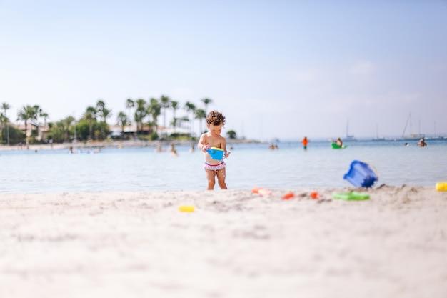 O bebê encaracolado pequeno bonito joga com água e areia na praia no beira-mar.