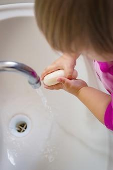 O bebê ensaboa as mãos e sai água da torneira.