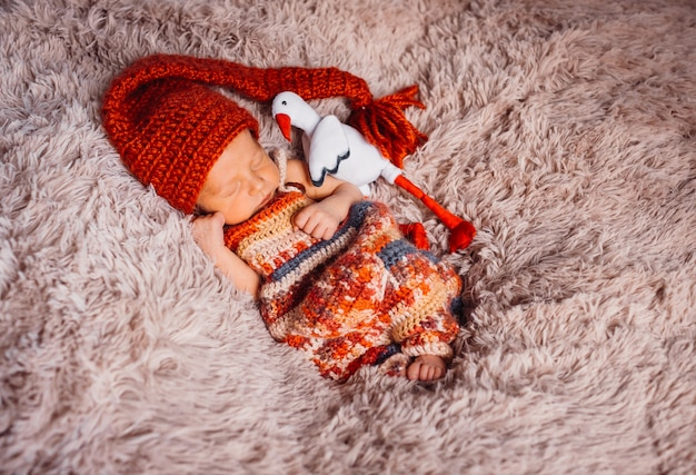 O bebê envolto em cachecol vermelho dorme no cobertor esponjoso