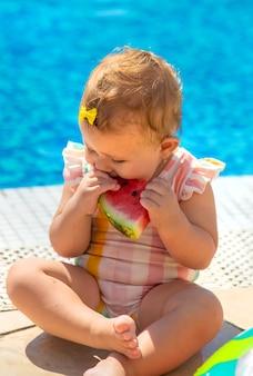 O bebê está comendo uma melancia à beira da piscina. foco seletivo. crianças.