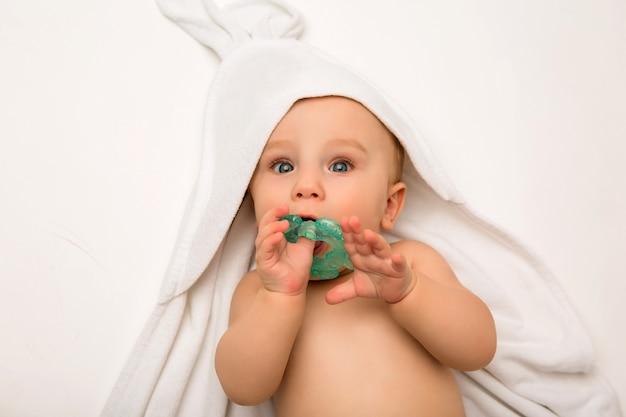 O bebê está deitado com um mordedor em uma toalha branca após o banho