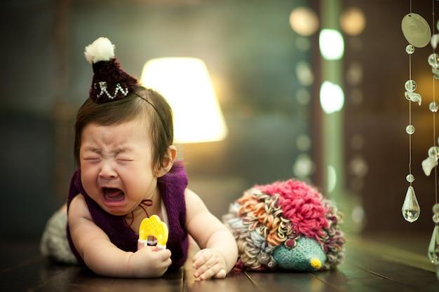 O bebê está deitado de bruços e está sofrendo.