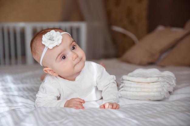 O bebê está deitado na cama no quarto, uma pilha de fraldas
