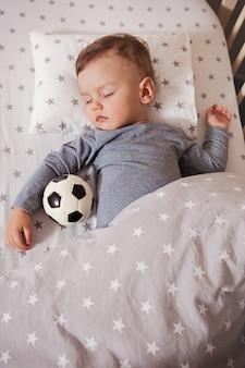 O bebê está dormindo em um berço com uma bola de futebol na mão.
