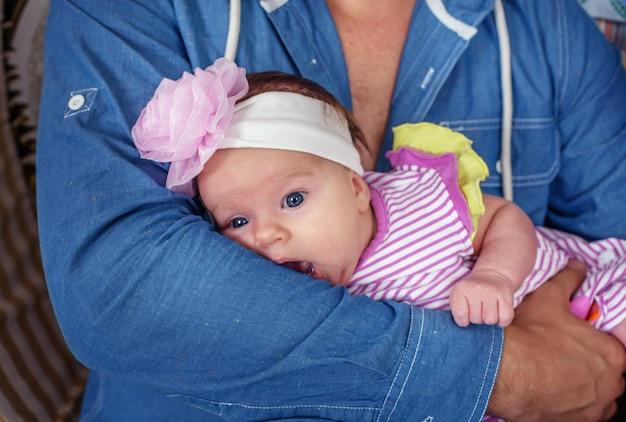 O bebê está nas mãos de seu pai.