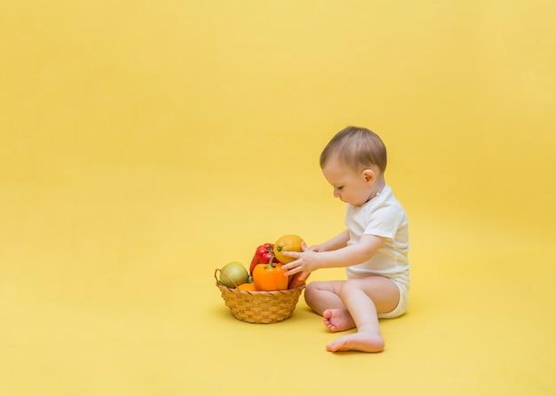 O bebê está sentado com uma cesta de frutas e legumes. o bebê está separando uma cesta de legumes e frutas em um espaço amarelo. copie o espaço