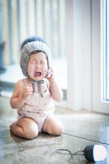 O bebê está sentado e chorando.