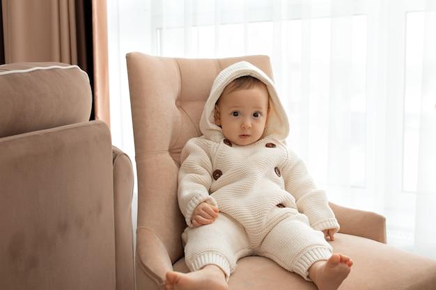 O bebê está sentado em uma cadeira com um macacão de tricô