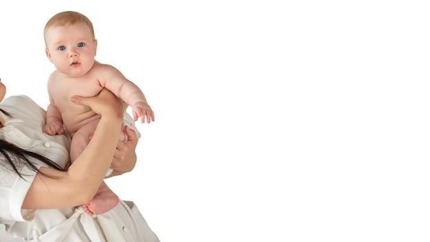 O bebê olha surpreso para a câmera, sentado nos braços da mãe sobre um fundo branco