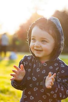 O bebé pequeno joga no parque no luminoso.