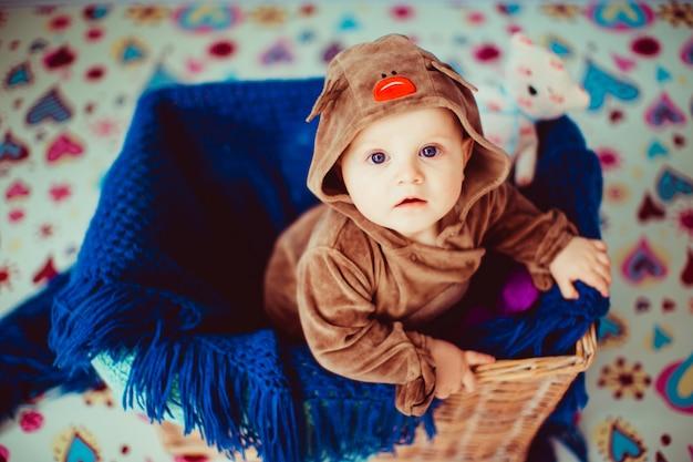 O bebê pequeno senta-se em uma cesta de vime.