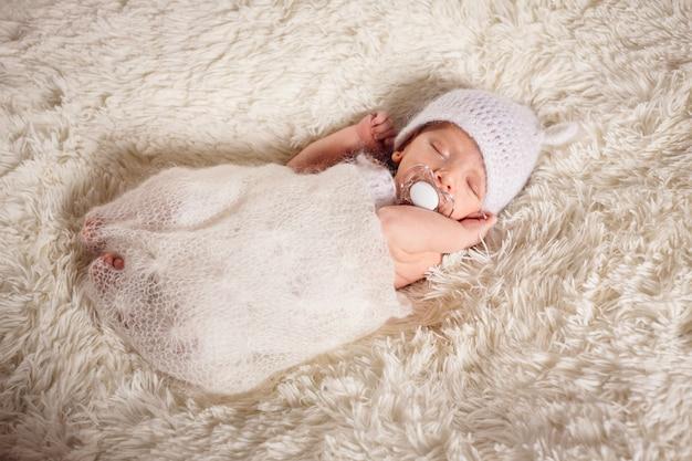 O bebê pequeno tem um manequim e encontra-se na cama