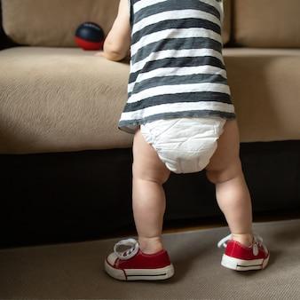 O bebê pratica esportes em casa com a bunda do bebê em uma fralda