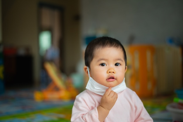 O bebê que veste a máscara cirúrgica fica em casa.