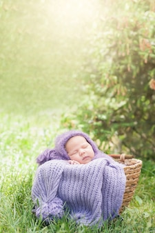 O bebê recém-nascido de sorriso 17 dias idoso está dormindo em seu estômago na cesta na natureza no jardim exterior.