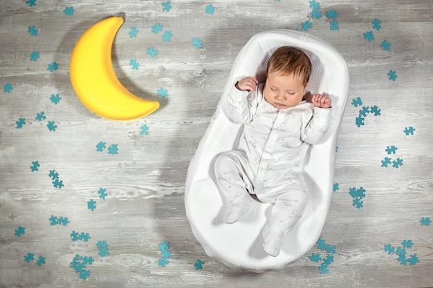 O bebê recém-nascido dorme em um colchão ortopédico especial baby casulo, em um piso de madeira, lua de brinquedo e quebra-cabeças. sono calmo e saudável em recém-nascidos.