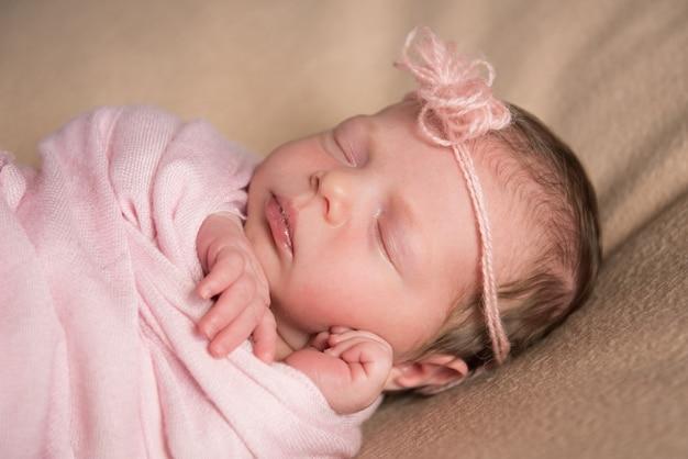 O bebê recém-nascido dorme sob uma capa de malha rosa. fechar-se