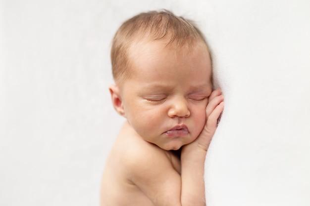 O bebé recém-nascido encantador está dormindo nas mãos brancas do fundo sob a face. criança deitada de lado