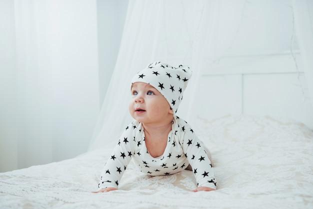 O bebê recém-nascido vestido com um terno branco e estrelas negras é uma cama macia branca no estúdio