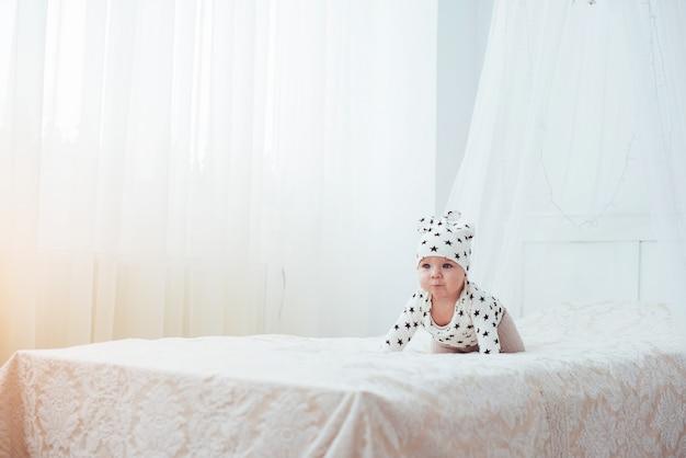 O bebê recém-nascido vestido com um terno branco e estrelas negras é uma cama macia branca