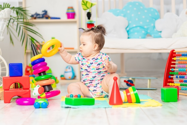 O bebê recolhe a pirâmide, a criança brinca em casa no berçário