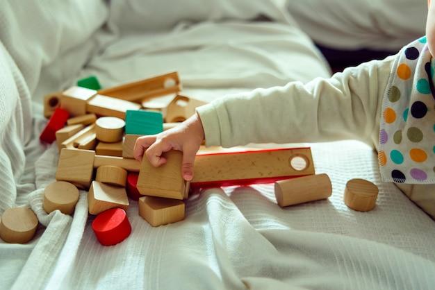 O bebê se diverte selecionando cubos de madeira para brincar com eles e desenvolver seus sentidos espaciais.