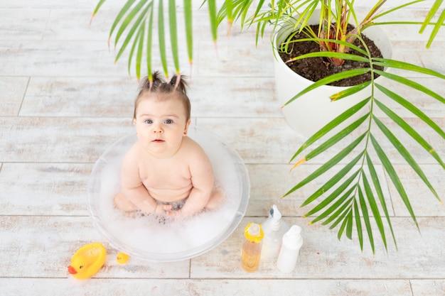 O bebê se lava em uma tigela com espuma