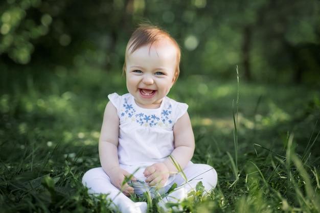 O bebê se senta na grama verde do parque e ri. os primeiros dois dentes do bebê