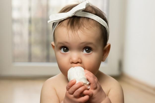 O bebê se senta no chão com a fralda e come marshmallows. proibida não é uma refeição saudável.
