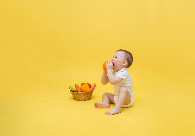 O bebê segura uma laranja na mão e faz uma careta com o gosto amargo. um menino está sentado com uma cesta de frutas e legumes. copie o espaço