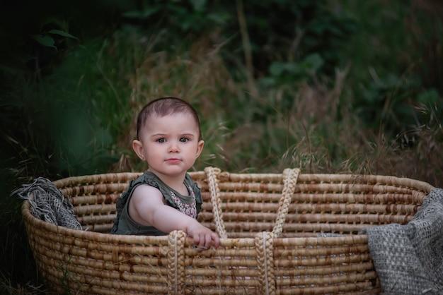 O bebê senta-se em um berço de palha de vime em um parque verde. menina com vestido bonito sorrindo. retrato.