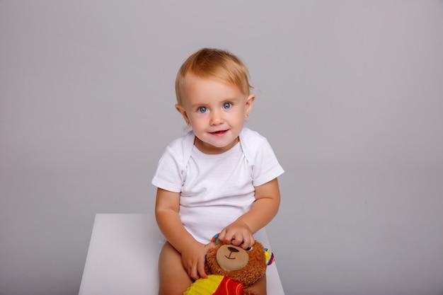 O bebê senta-se no cubo no estúdio branco,