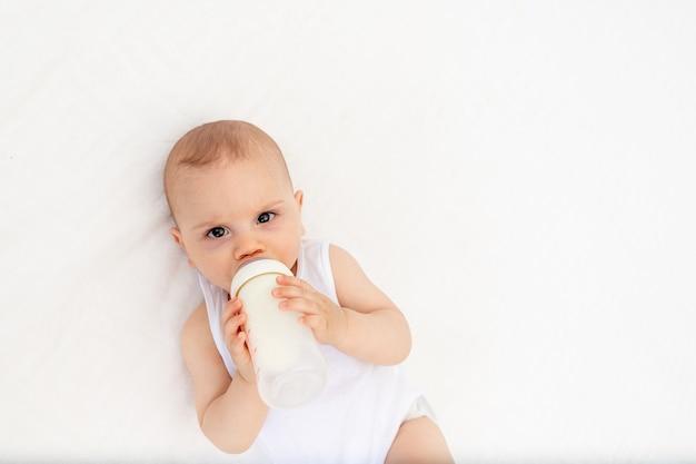 O bebê suga leite de uma mamadeira deitado em um berço no berçário em uma cama branca