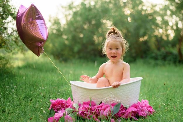 O bebê toma banho em um banho de leite na rua no verão. a garota abriu a boca surpresa.